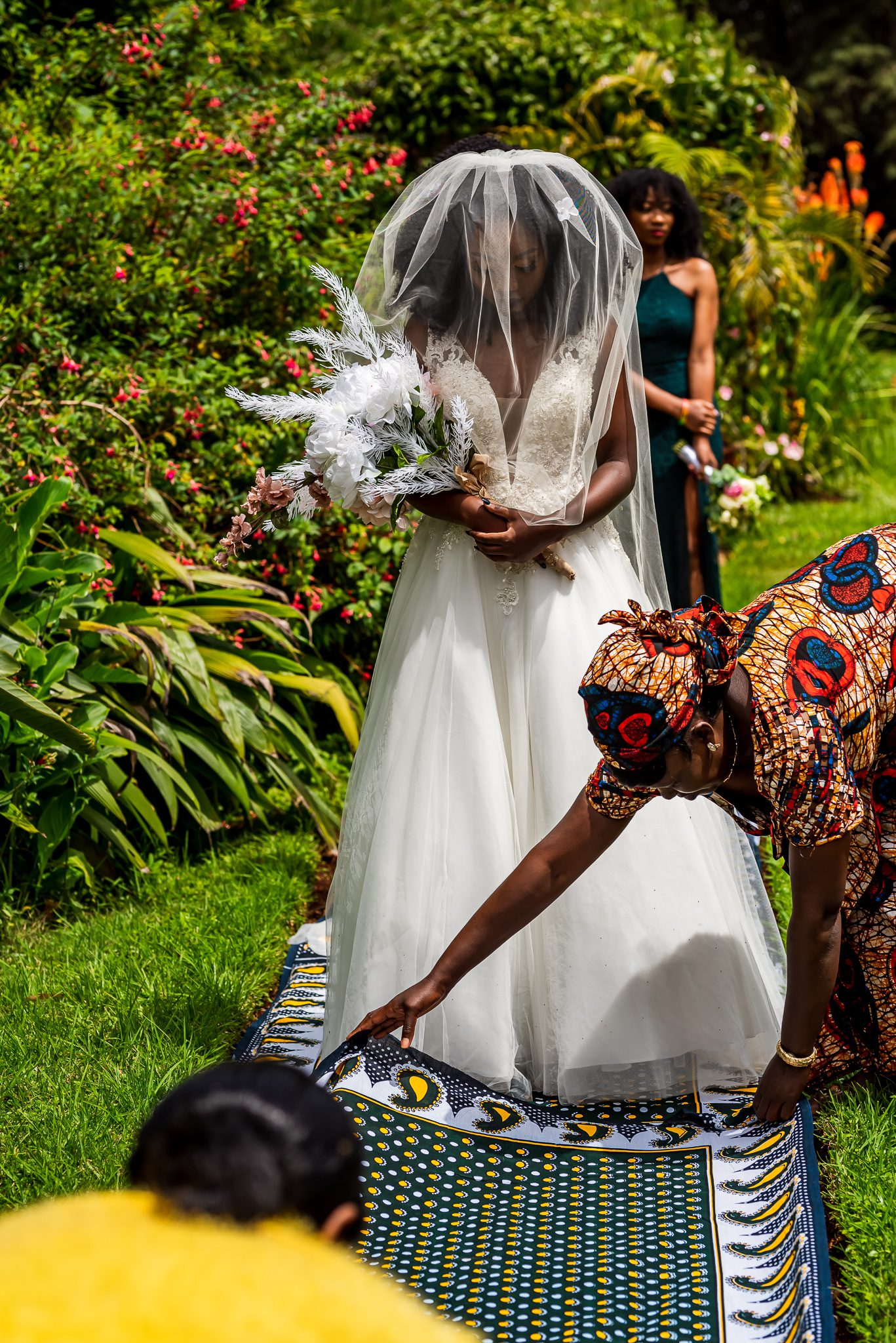 a woman lays a cloth down on the ground in front of a bride before she walks down the isle