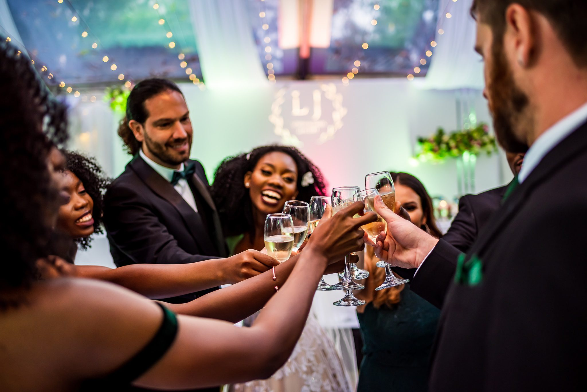 a bride and groom cheers champagne with their wedding attendants at their reception